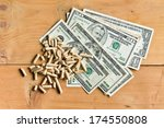 top view of pellets with american dollars on wooden background - stock photo
