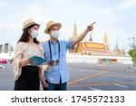 Small photo of Asian couple happy tourists to travel wearing mask to protect from Covid-19 on they holidays and holding travel map and pointing in Wat Phra Kaew Temple in Bangkok, Thailand