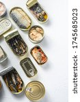 opened cans with different types of fish and seafood, opened and closed cans with Saury, mackerel, sprats, sardines, pilchard, squid, tuna, over white stone surface top view vertical space for text.