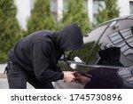 Car thief steal car breaking door criminal job burglar Hijacks  Auto thief black balaclava hoodie trying  break into vehicle screwdriver  Street crime violence gangster robber automobile parking - stock photo