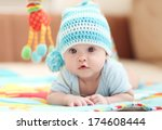 Stock photo little child lying on a children s rug in the white blue cap small depth of field dof 174608444