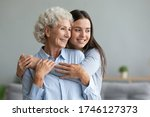 Small photo of Young caring grand daughter hugging to loving elderly grandmother, multi-generational relatives women standing look in window dreaming feels happy spend time together, love connection warmth concept