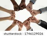 Small photo of Close up bottom view diverse employees team holding fists in circle, expressing unity and power in teamwork, multiethnic business people engaged in team building activity at briefing