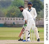Small photo of New Delhi India – March 3 2020 : Full length of cricketer playing on field during sunny day in local playground, Cricketer on the field in action, Players playing cricket match at field
