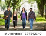 Stock photo full length of multiethnic friends walking on campus road 174642140