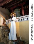 Small photo of Hue City, Thua Thien Hue Province, Vietnam - May 7, 2020: Photo of a girl in a traditional ao dai costume inside a temple in Hue City, Thua Thien Hue Province, Vietnam
