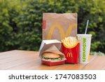 Small photo of Mykolaiv, Ukraine - May 2020 McDonald's food on the table on the green bush background. Big Mac menu. A McDonald's bag next to glass of cola, fried potatoes and a Big Mac burger