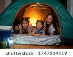 Small photo of Asian woman playing and staying in tent with her daughter and having fun with camping tent in their bedroom a staycation lifestyle a new normal for social distancing in coronavirus outbreak situation