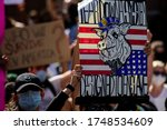 Small photo of Miami Downtown, FL, USA - MAY 31, 2020: Pig on a background of American flag picture. Teardown racism, designed to enslave poster sign on demonstrations. Revolt against the police