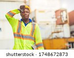 Small photo of Tired stress worker sweat from hot weather in summer working in port goods cargo shipping logistic ground, Black African race people.