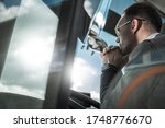 Confused and Pensive Bus Coach Driver Behind Vehicle Wheel Thinking About the Future of His Transportation Business. - stock photo