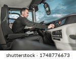 International Bus Driver Preparing For Another Trip. Caucasian Motor Coach Driver in His 30s Inside Modern Bus Vehicle. - stock photo