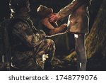 Army and Patriotism Theme. Soldier Giving Teddy Bear Toy to Caucasian Girl in Dark Foggy Forest - stock photo