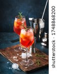 Small photo of Milano spritzer italian alcoholic cocktail with red bitter, dry white wine, soda, zest and ice. Blue background, steel bar tools, copy space