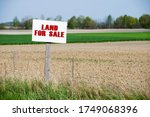 A Sign Is In Front Of The Land. ...