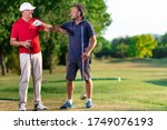 Small photo of two golfers greet each other by touching their elbows - golf friends say hello at the time of the covid