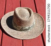 Straw Sun Hat On Red Deck Boards