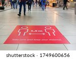 """Small photo of Selected focus low angle view at """" Keep your distance"""", on red rectangular caution sign on the floor inside Main Train Station in Germany during Social Distancing by epidemic of COVID-19."""