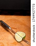 Small photo of Top, front view, close up of a serrated knife slicing a local, freshly picked, ripe lime, on a wood cutting board
