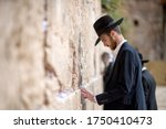 Small photo of The Western Wall Jerusalem, Israel. April 25, 2018. A Jewish Orthodox Judaism Man with a black touching the Wailing Wall with his hands to pray.