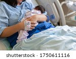 Small photo of Asia Chinese Mother holding her newborn child after labor in hospital wad room
