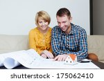 Young happy couple sitting on a sofa and looking at a blueprint - stock photo