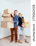 Young couple holding carton boxes and moving in - stock photo