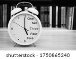 Small photo of The table clock alarm clock in the foreground is arranged closeup against the blurred background of the book shelf and shows a time of 5 five or 17 seventeen hours