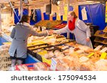 ZWOLLE, THE NETHERLANDS - FEBRUARY 1, 2014: Unidentified woman buying bread at the street market in Zwolle. In the Netherlands there are 18,000 merchants realizing a 2.6 billion turn over. - stock photo