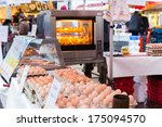 ZWOLLE, THE NETHERLANDS - FEBRUARY 1, 2014: Eggs on display and chicken roasting at the street market in Zwolle. In the Netherlands there are 18,000 merchants realizing a 2.6 billion turn over. - stock photo