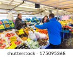ZWOLLE, THE NETHERLANDS - FEBRUARY 1, 2014: Unidentified man buying groceries at the street market in Zwolle. In the Netherlands there are 18,000 merchants realizing a 2.6 billion turn over. - stock photo