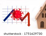 Small photo of A cardboard house besides a downtrend graph,to symbolize properties price downfall during pandemic.