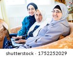 Small photo of Happy arabic muslim grandmother and grand daughter and mother sitting togther on couch using technology