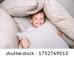 Small photo of Little funny kid built impromptu fort house of pillows and blankets on bed.