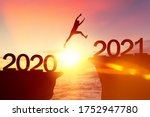 Small photo of Silhouette man jumping between cliff with number 2020 to 2021 at tropical sunset beach. Freedom challenge and travel adventure holiday concept. Vintage tone filter effect color style.