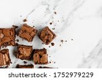 Small photo of A Batch of Brownies Cut into Squares, arranged from the Left in a Messy Way Close Up, with Crackling Crust on a White Marble Background Shot from Above