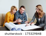 Young couple discussing the layouts of a future house with an architect - stock photo