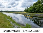 two canoeists sitting in a canoe and paddling on a canal