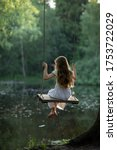 Small photo of A girl in the forest swinging on a swing. Rope swing on a forest lake. Barefoot girl in a white dress with long hair