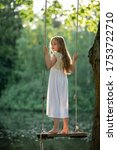Small photo of A girl in the forest swinging on a swing. Girl stands on a swing. Rope swing on a forest lake. Barefoot girl in a white dress with long hair