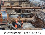 Small photo of Russia, Samara - May 21, 2020. Construction site with earthwork for the replacement of water pipes, heating mains and sewers. Construction workers fasten the pipe to the hook of a construction crane.
