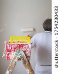 Painter working in a room. The colorman is painting a wall using a paint roller, paint tray, paint scuttle and a ladder