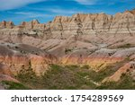 Reds, yellows, oranges and browns color the arid rocks, ridges and cliffs in the rugged Badlands of South Dakota.