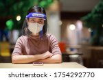 Small photo of Asian woman in face shield,medical face mask outbreak,. Having absent-mindedness or depression that results from status pandemic risk Corona virus disease COVID-19 infection. Concept new normal.