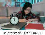 Small photo of closeup of a clock against blurred background of a diligent japanese girl burning midnight oil. asian female student still up studying late at night