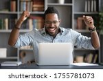 Small photo of African guy feels happy received great news by internet looks at pc screen raised hands scream with joy celebrating on-line lottery win, successful admission to college, offers big discounts concept