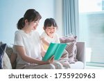 Small photo of Mother and daughter sitting on the sofa and reading a picture book