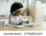 Small photo of In kitchen schoolgirl do homework, focused little African girl wear headphones watch video lesson using laptop app, interested in on-line web virtual class studying from at home, homeschooling concept