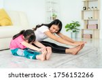 Small photo of Asian Mother and daughter doing fitness exercises in living room at home to maintain physical and mental health and wellbeing get exercise into your daily routine while social distancing.
