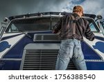 Caucasian Commercial Driver in His 40s Checking Truck Windshield Wipers in His Vehicle. Trucker and His Job. Semi Maintenance. - stock photo